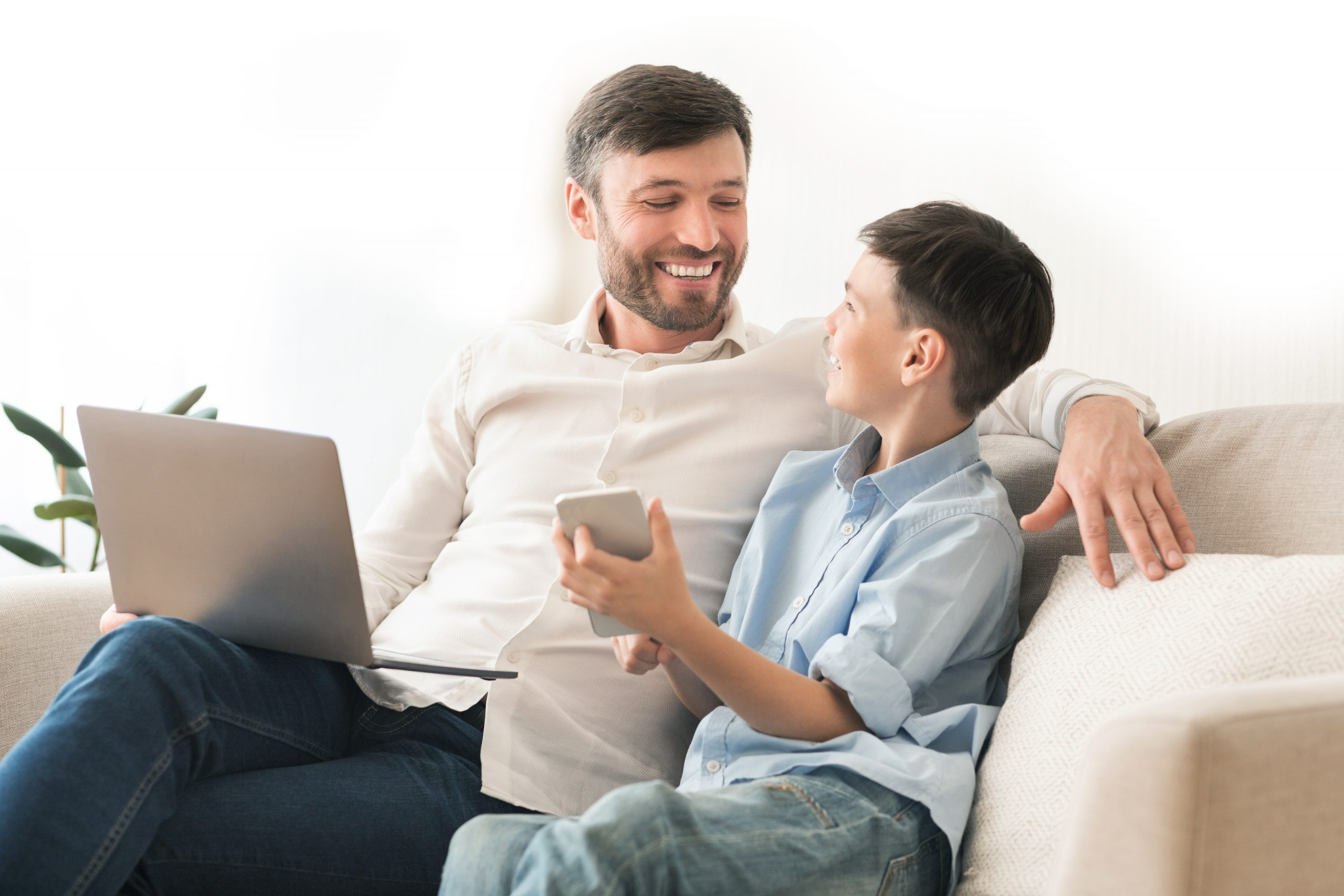 Father and son sitting on couch with laptop and smartphone